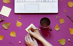 Woman`s hand is writing on the note paper on the conceptual autumn background. Stock Images