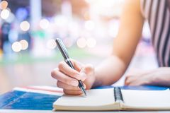Woman`s hand writing on a notebook with a pen on a wooden desk. Stock Photography