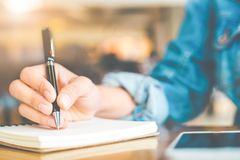 Woman`s hand writing on a notepad with a pen on a wooden desk. Stock Photography