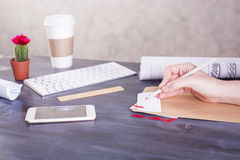 Woman's hand writing on paper. Side view of woman's hand writing on paper placed on wooden desktop with smart phone, coffee cup, computer keyboard, cactus and royalty free stock photos