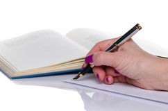 Woman's hand writing on paper. On white Stock Photography