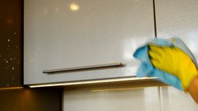 Woman`s hand in a yellow rubber glove cleans the surface of a modern plastic kitchen Cabinet with detergent and a cloth. The conce stock video