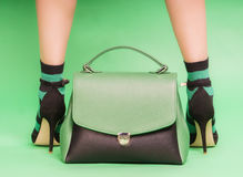 Woman`s handbag in green and black colors. With legs of woman in socks on green background Stock Photo