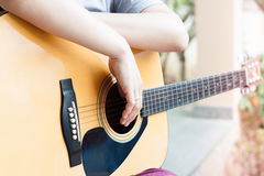 Woman's hands with acoustic guitar in relax post Stock Image