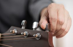 Woman`s hands adjusting acoustic guitar. stock photo