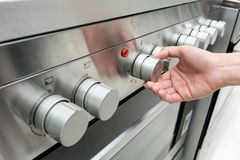 Free Woman`s Hands Adjusting Heat Button On Oven Machine Stock Photos - 105500803