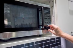 Woman`s Hands adjusting timing button on microwave. For cooking stock images