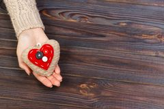 Woman`s hands with beautiful accurate knitted red heart. White cozy knitted sweater on wooden background. Concept of giving help. Love concept with copyspace Stock Photos