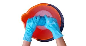 Woman`s hands in blue gloves wringing blue microfiber towel into orange bucket filled foam liquid. stock image