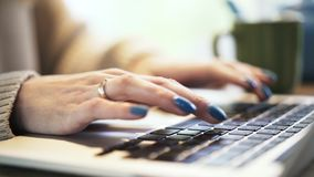 Woman s hands with blue nail polish typing at laptop, pan shot stock video footage