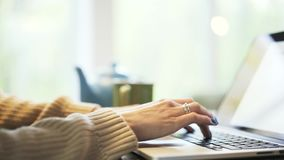 Woman s hands with blue nail polish typing at laptop, tilt down stock footage