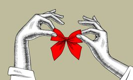 Woman`s hands with bow of red ribbon. Vintage engraving stylized drawing. Vector illustration Stock Image