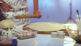 Woman`s hands with bracelets and rings roll out dough on board with rolling pin. Woman in her late 40s dressed in colorful apron is rolling out dough on large stock video footage