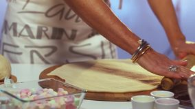 Woman`s hands with bracelets roll out dough on big wooden board with rolling pin. Woman in her late 40s dressed in white and grey apron is rolling out dough on stock video