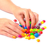 Woman's hands with bright manicure taking a colorful candy Royalty Free Stock Photography