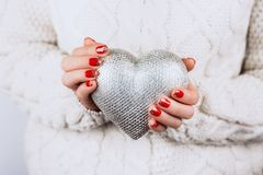 Woman`s hands carefully keep silver heart. Woman`s hands with beautiful accurate manicure carefully keep silver heart stock images