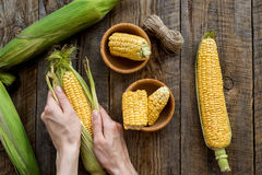 Woman`s hands clean corn cob. Rustic wooden background top view Royalty Free Stock Photo