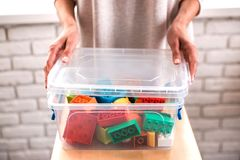 Woman`s hands putting colored blocks into box. royalty free stock photos
