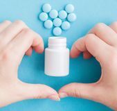 Woman`s hands created a heart shape. White pills. Mock up for special offers as advertising or other ideas. Medical and healthcar. E concept. Copy space. Empty royalty free stock photos