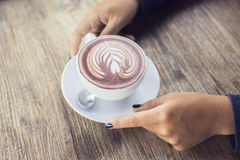 Woman's hands with a cup of cappuccino Royalty Free Stock Photos