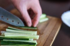 Woman& x27;s Hands Cut Cucumber Matchsticks with Santoku Knife on a Wooden Chopping Board. Salads, Maki and Temaki Sushi Rolls. Woman's Hands royalty free stock images