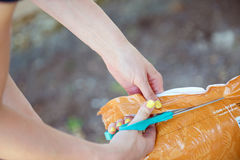 Woman's hands cut open a large bag. In the shade Royalty Free Stock Photo
