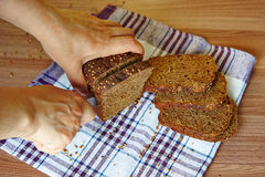 Woman`s hands cut rye bread Stock Photography
