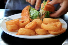 Woman's hands cutting burger, with crispy onion rings as a side dish Royalty Free Stock Image