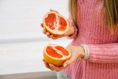 Woman`s hands cutting fresh grapefruit on kitchen. Girl cutting orange with knife. Healthy lifestyle concept. stock photo
