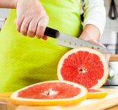 Woman's hands cutting grapefruit Royalty Free Stock Photos