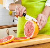 Woman's hands cutting grapefruit Stock Image