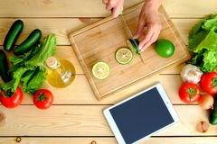 Woman's hands cutting green lime on wooden board with tablet Stock Images
