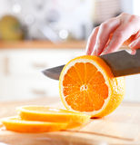 Woman's hands cutting orange Royalty Free Stock Photo