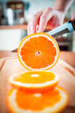 Woman's hands cutting orange Stock Photos