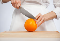 Woman's hands cutting ripe orange Stock Photo