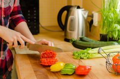 Woman's hands cutting tomato on the kitchen, other fresh vegetab