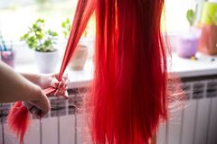 Woman`s hands delicately combing red hair, messy wig on the stand. royalty free stock photos