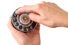 Woman's hands with a dialer. A rotary dial is a component of a telephone or a telephone switchboard that implements a signaling technology in telecommunications royalty free stock images