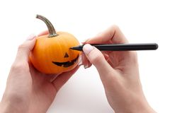 Woman`s hands drawing scary face on a little pumpkin stock photography