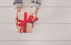 Woman`s hands give christmas gift in present box Royalty Free Stock Photography