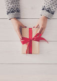 Woman`s hands give christmas gift in present box Stock Image