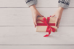 Woman`s hands give christmas gift in present box Stock Photo