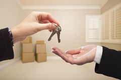 Woman's Hands Handing Over the House Keys Inside Empty Tan Room Royalty Free Stock Photo