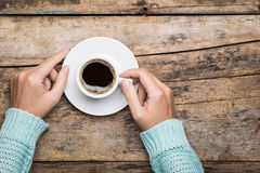 Woman's hands hold a cup of strong coffee. Stock Image