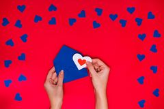 Woman`s hands hold envelope with love letter above red background. With many blue hearts around. Love concept Royalty Free Stock Photos