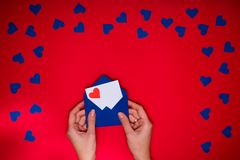 Woman`s hands hold envelope with love letter above red background. With many blue hearts around. Love concept Royalty Free Stock Image