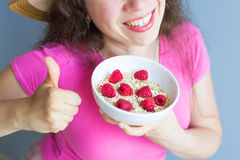 Woman`s hands hold healthy and natural breakfast, oatmeal and raspberries in a bowl.  Royalty Free Stock Photos