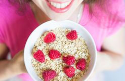 Woman`s hands hold healthy and natural breakfast, oatmeal and raspberries in a bowl.  Stock Images