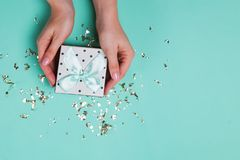 Free Woman`s Hands Holding A Gift Box On On Turquoise Background With Golden Confetti Royalty Free Stock Photography - 164225267