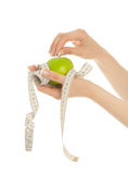 Woman's hands holding apple with measuring tape Royalty Free Stock Image